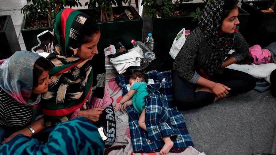 Mujeres refugiadas sentadas junto a un bebé dormido, entre las familias afganas que llegaron del campamento de Moria en la isla de Lesbos, a un campamento situado en una plaza del centro de Atenas, este junio.