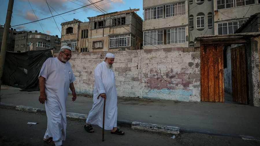 Dos ancianos palestinos caminan por una calle del campamento de refugiados de Al Shatea, en medio de la actual pandemia del coronavirus COVID-19 en la ciudad de Gaza.