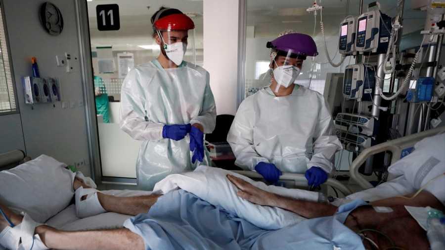 Dos sanitarios atienen a un paciente ingresado en plena pandemia