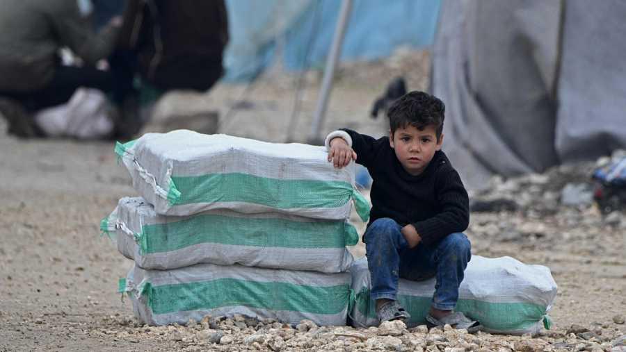 Un niño sirio desplazado sentado junto a paquetes de ayuda humanitaria