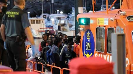 Un grupo de inmigrantes irregulares llega a puerto donde les toman la temperatura.