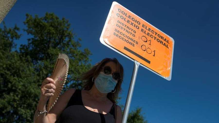 Elecciones gallegas 2020: Una mujer combate el calor junto a una señal de colegio electoral en Pereiro de Aguiar (Ourense).