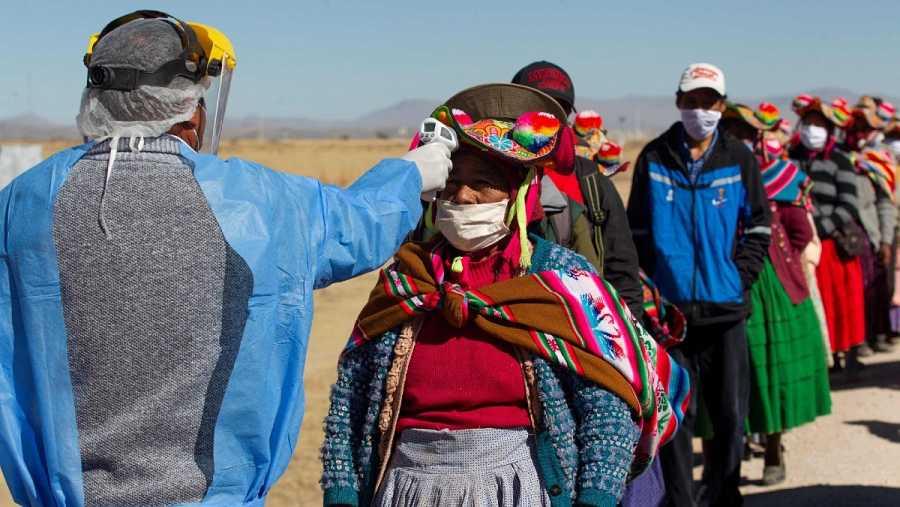 Trabajadores sanitarios comprueban la temperatura a los residentes de las comunidades vecinas a un mercado en Coata, cerca de la frontera con Bolivia, donde se ha detectado un brote del virus.