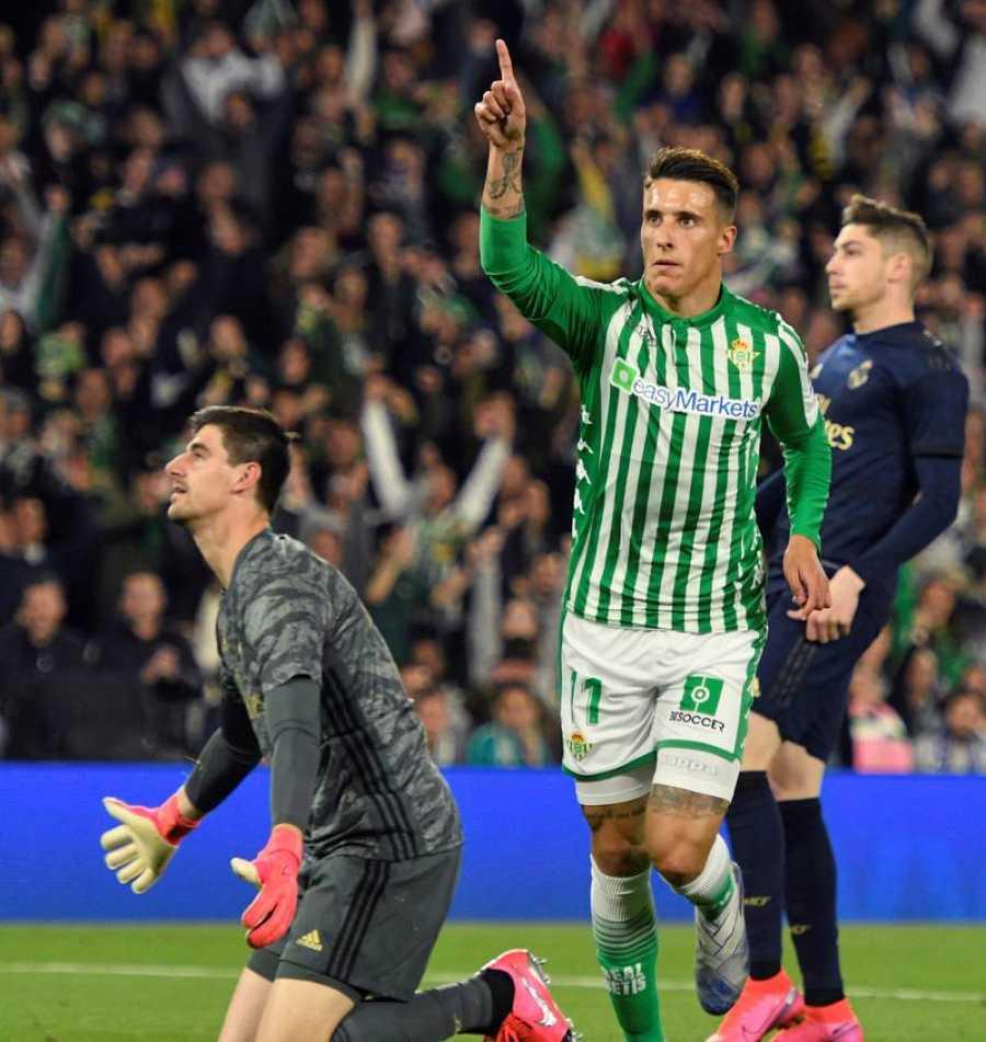El delantero del Real Betis Cristian Tello (d) celebra ante el guardameta belga del Real Madrid Thibaut Courtois el segundo gol del equipo sevillano