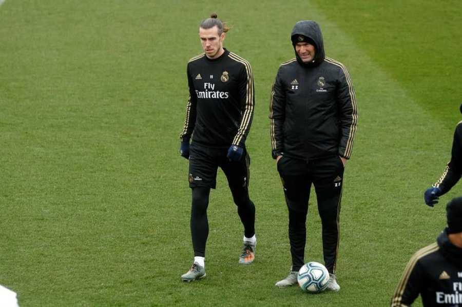 El entrenador francés del Real Madrid, Zinedine Zidane (d) junto al jugador galés Gareth Bale (i), en la previa del partido de la decimoctava jornada de LaLiga