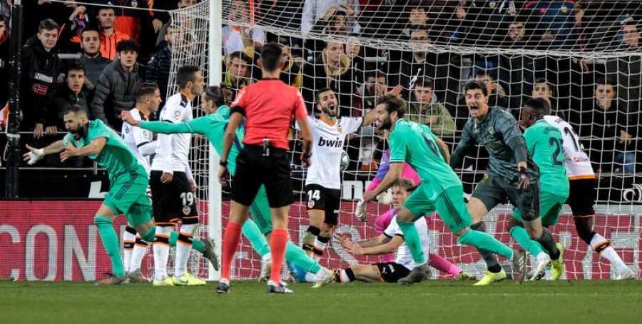 El delantero del Real Madrid Karim Benzema (i) celebra su gol, conseguido en el último minuto del partido ante el Valencia CF, durante el partido correspondiente a la 17ª jornada de LaLiga