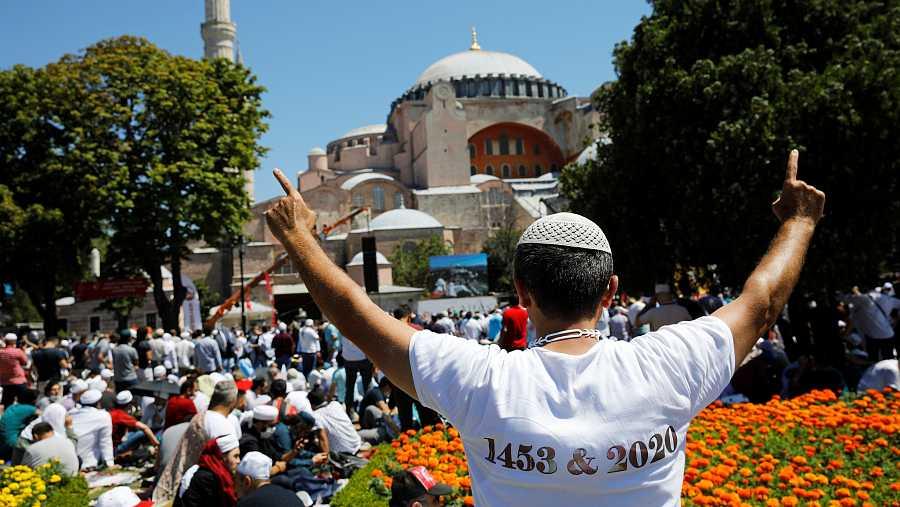 Un hombre hace un gesto de alegría mientras la gente espera el comienzo de las oraciones del viernes fuera de la Gran Mezquita de Santa Sophia, por primera vez después de que una vez más fuera declarada mezquita después de 86 años, en Estambul, Turqu