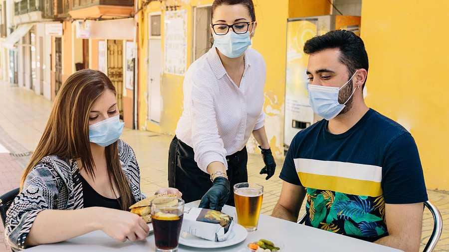 Una camarera atiende a dos clientes en la terraza de un bar con mascarilla.
