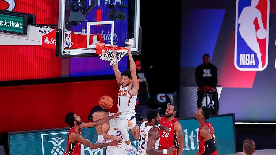 El escolta de los Phoenix Suns, Devin Booker hace un mate durante el partido contra los Miami Heat