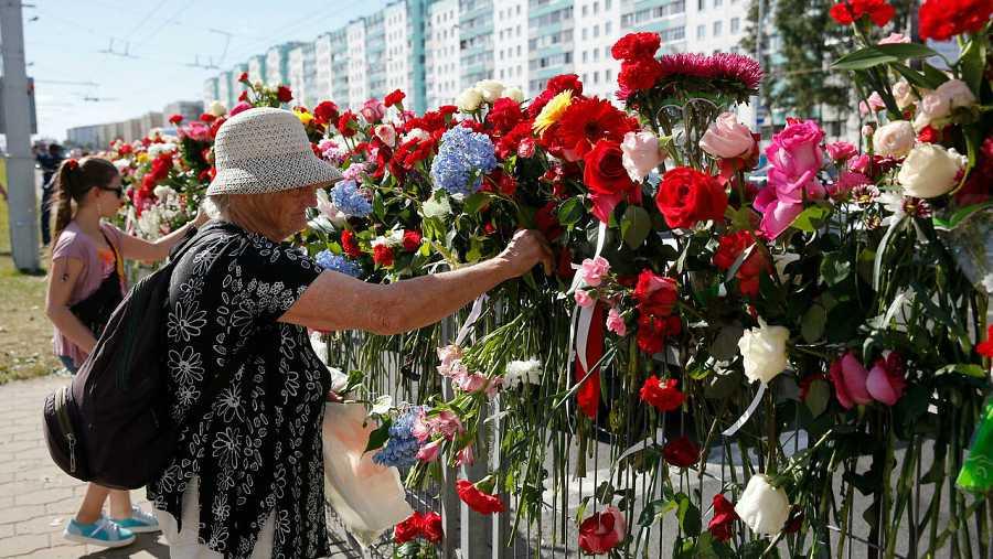 Personas depositan flores en el lugar donde murió un manifestante bielorruso en las protestas de la noche anterior en Minsk.