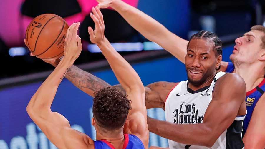 El alero de LA Clippers, Kawhi Leonard en acción frente a Nikola Jokic y Michael Porter