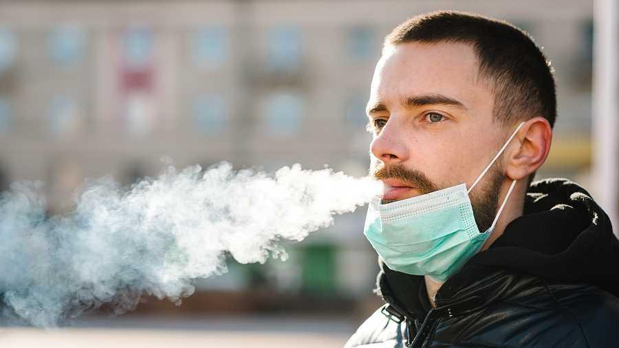 Joven fumando con mascarilla en la barbilla