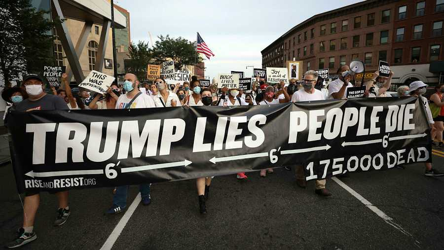 Las personas se reúnen para una vigilia y una 'Marcha por los Muertos' por las víctimas de la pandemia de coronavirus, en Brooklyn, Nueva York, EE. UU. con una pancarta que dice