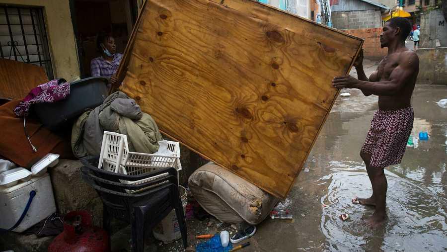 Una pareja saca algunas de sus pertenencias a la calle para que se sequen después de que su hogar se inundara debido a las intensas lluvias en Santo Domingo (República Dominicana).