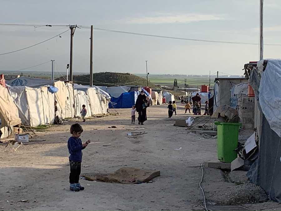 Unos niños caminan entre las tiendas del campo de Roj