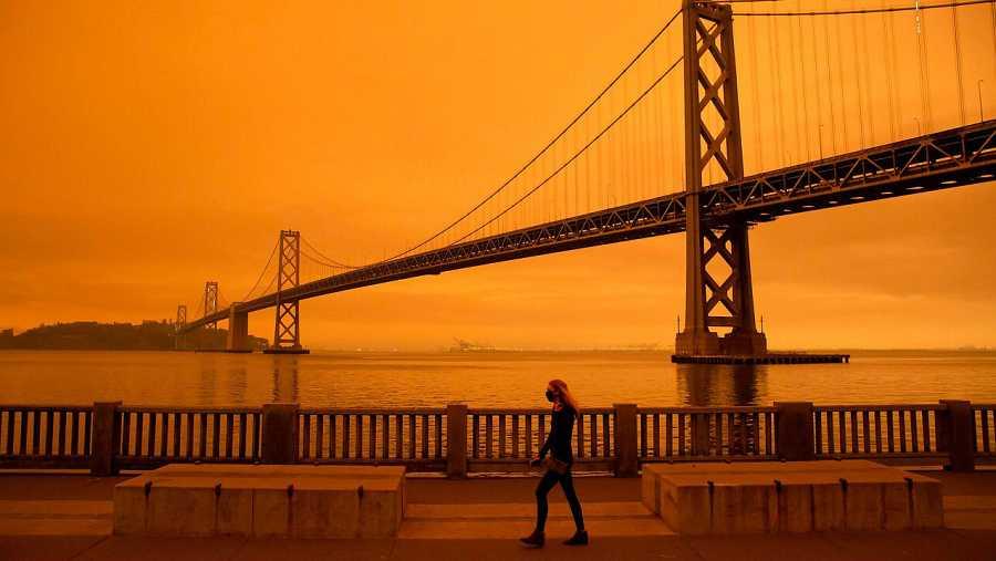 El puente de la bahía de San Francisco y el horizonte de la ciudad están oscurecidos por el humo naranja y la bruma como se ven desde Treasure Island, en San Francisco, California.
