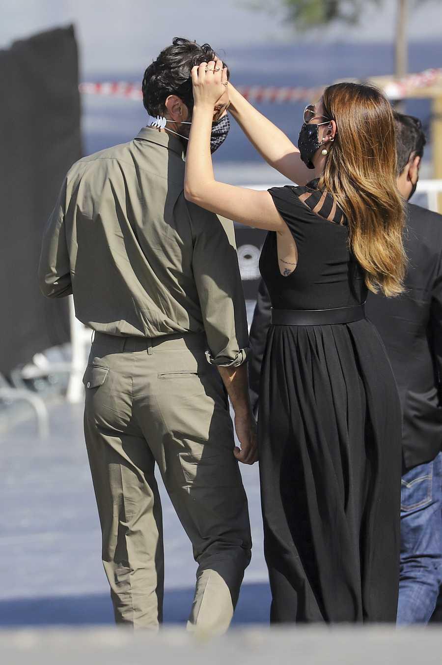 Blanca Suárez peina con las manos a Javier Rey cuando van a posar ante los medios en el Festival de San Sebastián