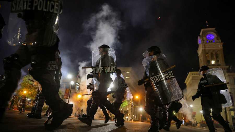 Los oficiales de policía pasan por el Ayuntamiento de Louisville cuando se implementa un toque de queda a las 9 de la noche para dispersar a los manifestantes en Louisville, Kentucky, EE.UU.