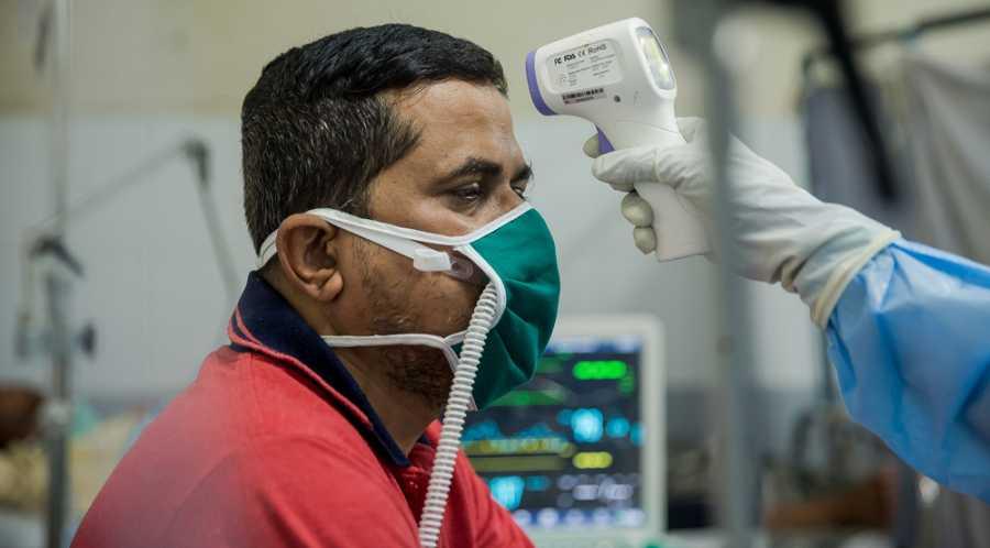 El Dr. Ilham toma la temperatura a un paciente ingresado en la unidad de pacientes de COVID-19.