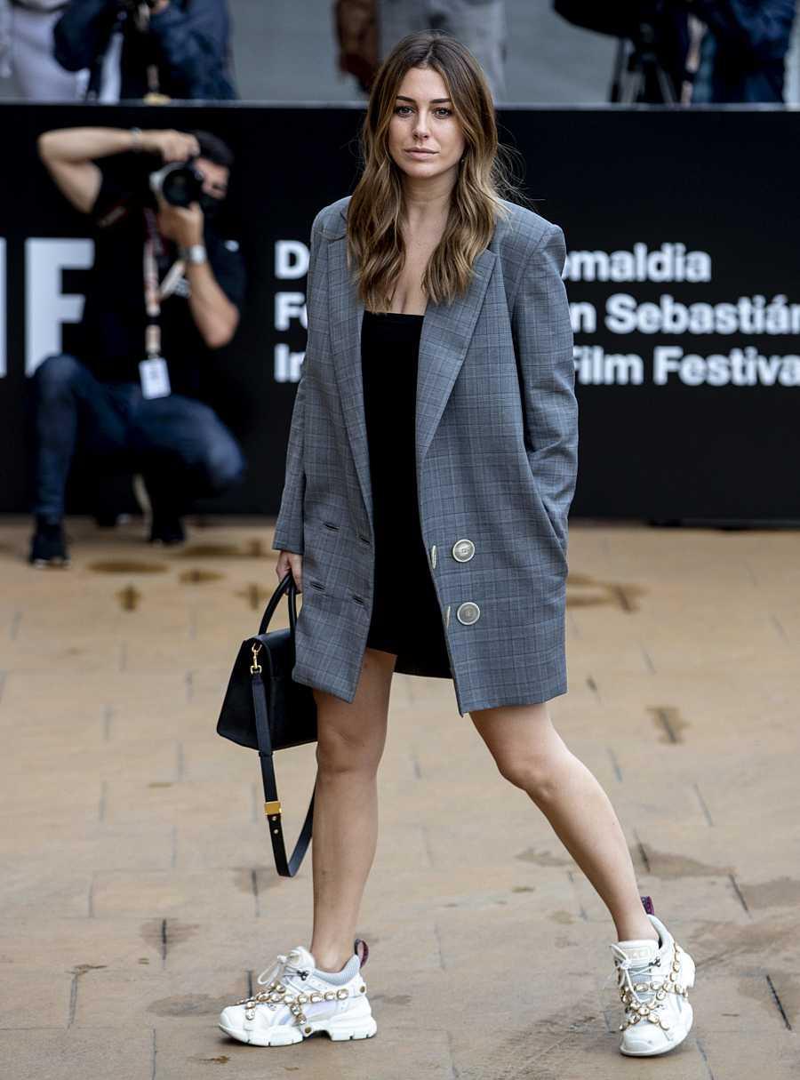 Blanca con una perfecta combinación de estilos luciendo unas zapatillas enjoyadas y un vestido blazer oversize