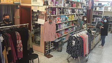 Carlos y Gema, mientras atienden a una clienta en su tienda de confecciones.