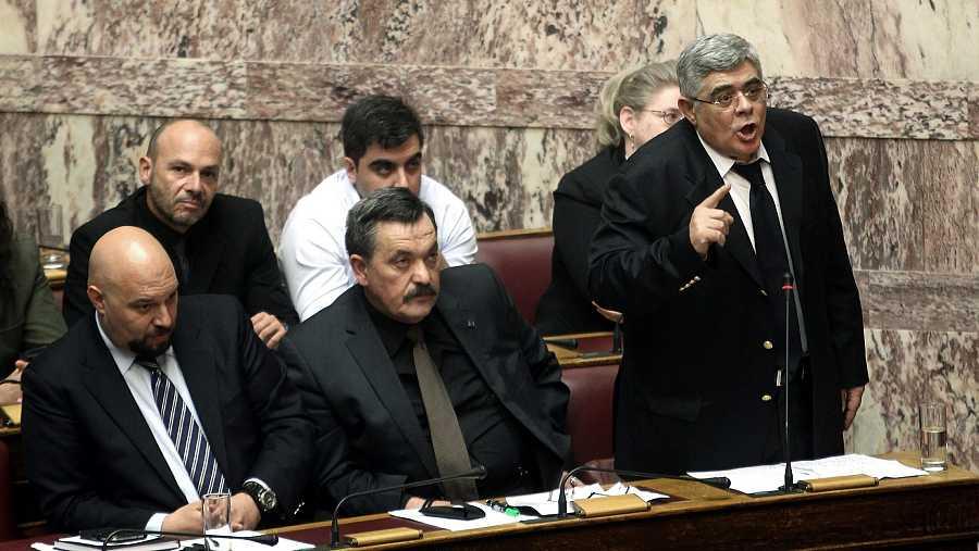 El líder del partido neonazi, Nikos Michaloliakos (d) durante una sesión plenaria del parlamento (Foto archivo)