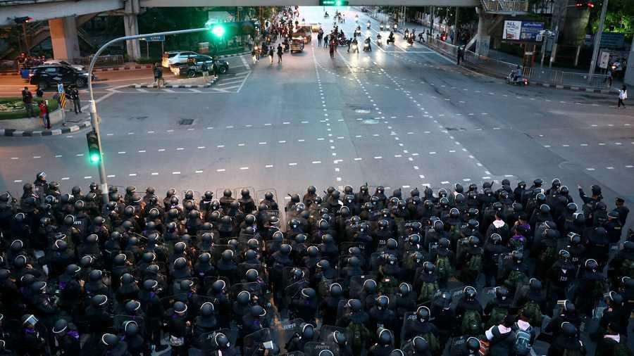 La policía antidisturbios toma posiciones después de un enfrentamiento con manifestantes antigubernamentales durante una protesta en el 47 aniversario del levantamiento estudiantil de 1973, en Bangkok, Tailandia.