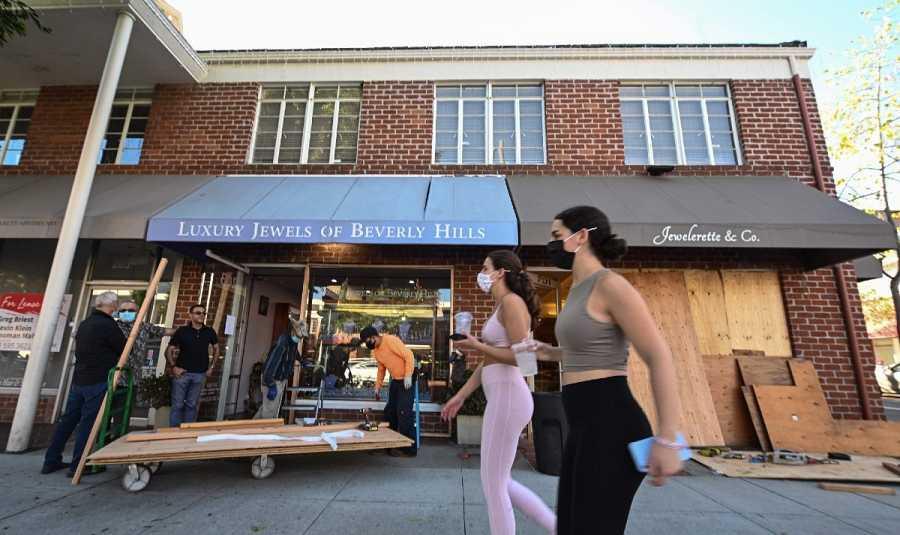 Dos mujeres pasan ante una joyería que tapia sus escaparates por los posibles disturbios en la noche electoral, Beverly Hills, California.
