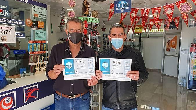 Jesús Sánchez padre e hijo posan junto a los dos quintos premios de Navidad vendidos en Roquetas