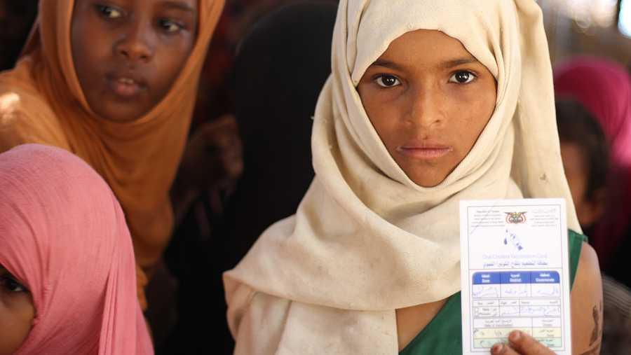 Una niña yemení muestra su cartilla de vacunación.