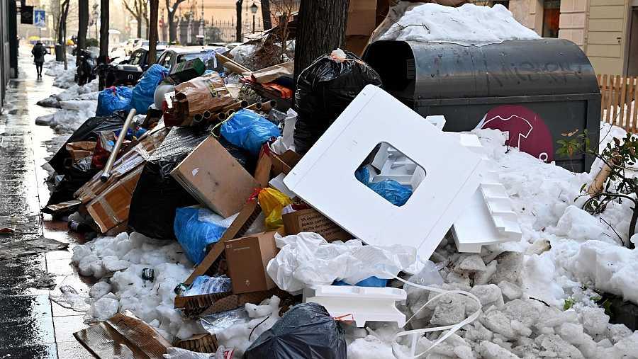 Bolsas de basura se amontonan alrededor de los contenedores en una calle de Madrid.