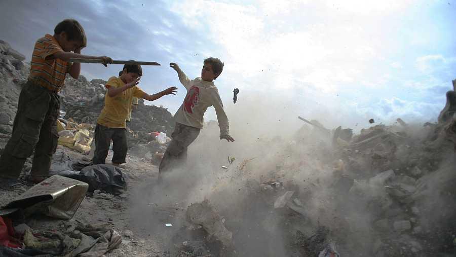Un grupo de jóvenes recogen metal y plásticos entre los escombros en Alepo (Siria)
