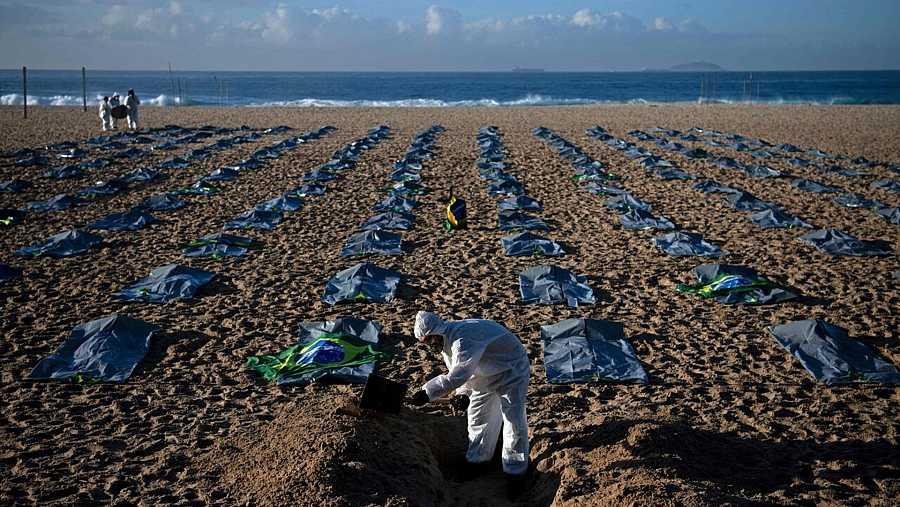 Activistas de la ONG pro-derechos humanos Rio de Paz cavan tumbas simbólicas en la playa de Copacabana, en Río de Janeiro, para protestar por la gestión de la pandemia por el gobierno de Jair Bolsonaro. CARL DE SOUZA / AFP