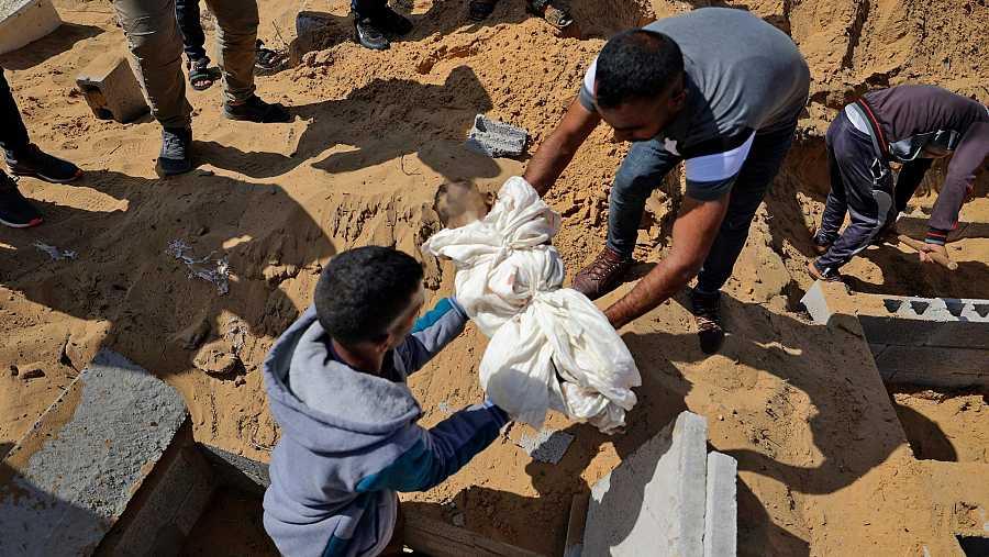 Hombres palestinos trasladando el cadáver de un niño pequeño que falleció en un ataque aéreo israelí
