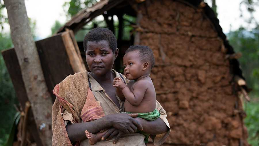 Janvière Kangoro sostiene aEstela, uno de sus cuatro hijos, frente al refugio en el que ahora viven.