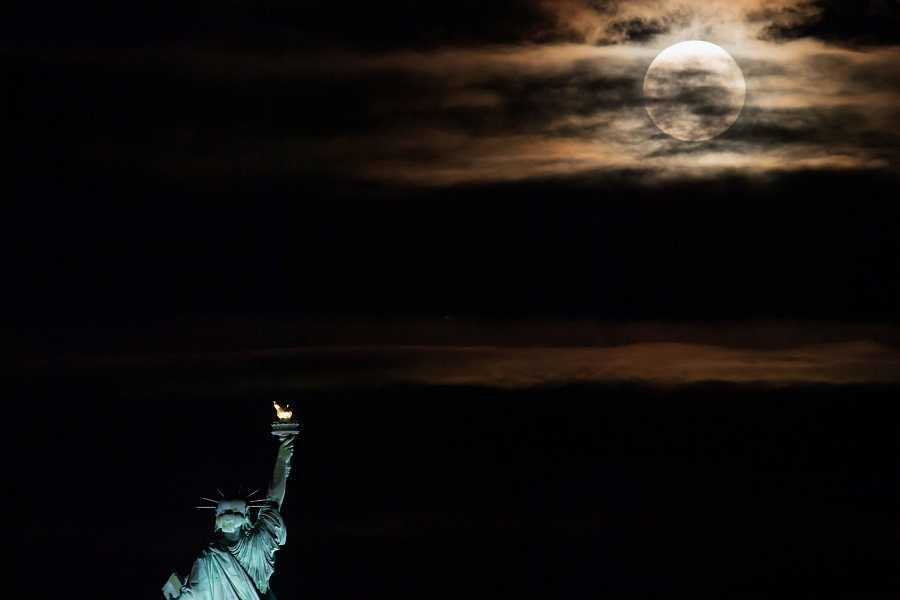 La primera luna llena del verano asoma por detrás de la estatua de la libertad de Nueva York