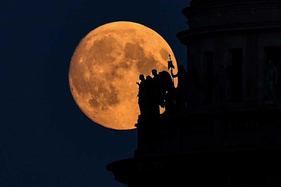 La luna llena de la fresa, detrás de las esculturas de la catedral de San Isaac en San Petersburgo