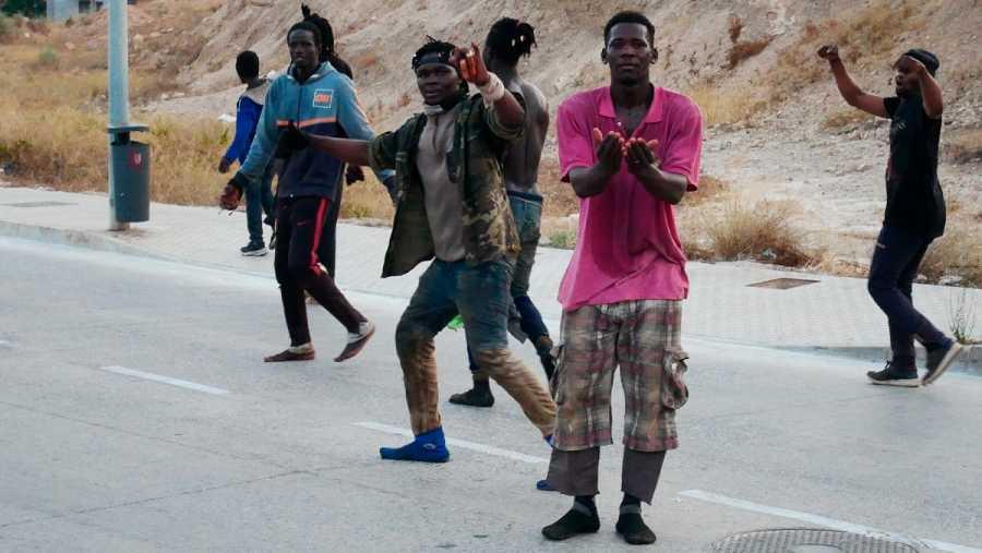 Varios migrantes celebran haber conseguido saltar la valla fronteriza