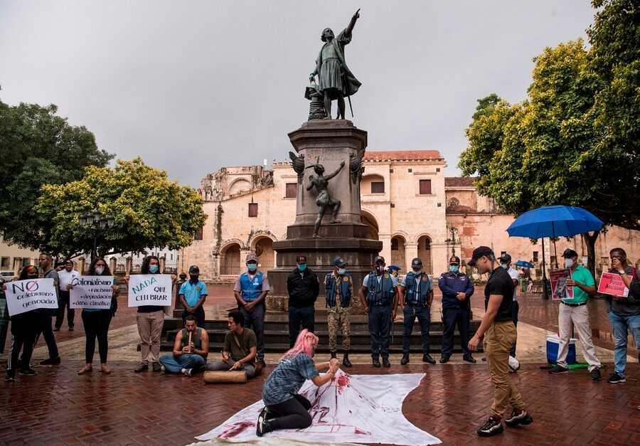 Personas protestan junto a una estatua de Cristóbal Colón en Santo Domingo