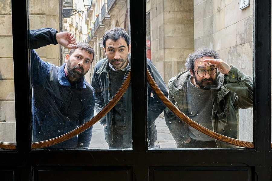 Els tres membres de Mujeres mirant a través del vidre d'una porta