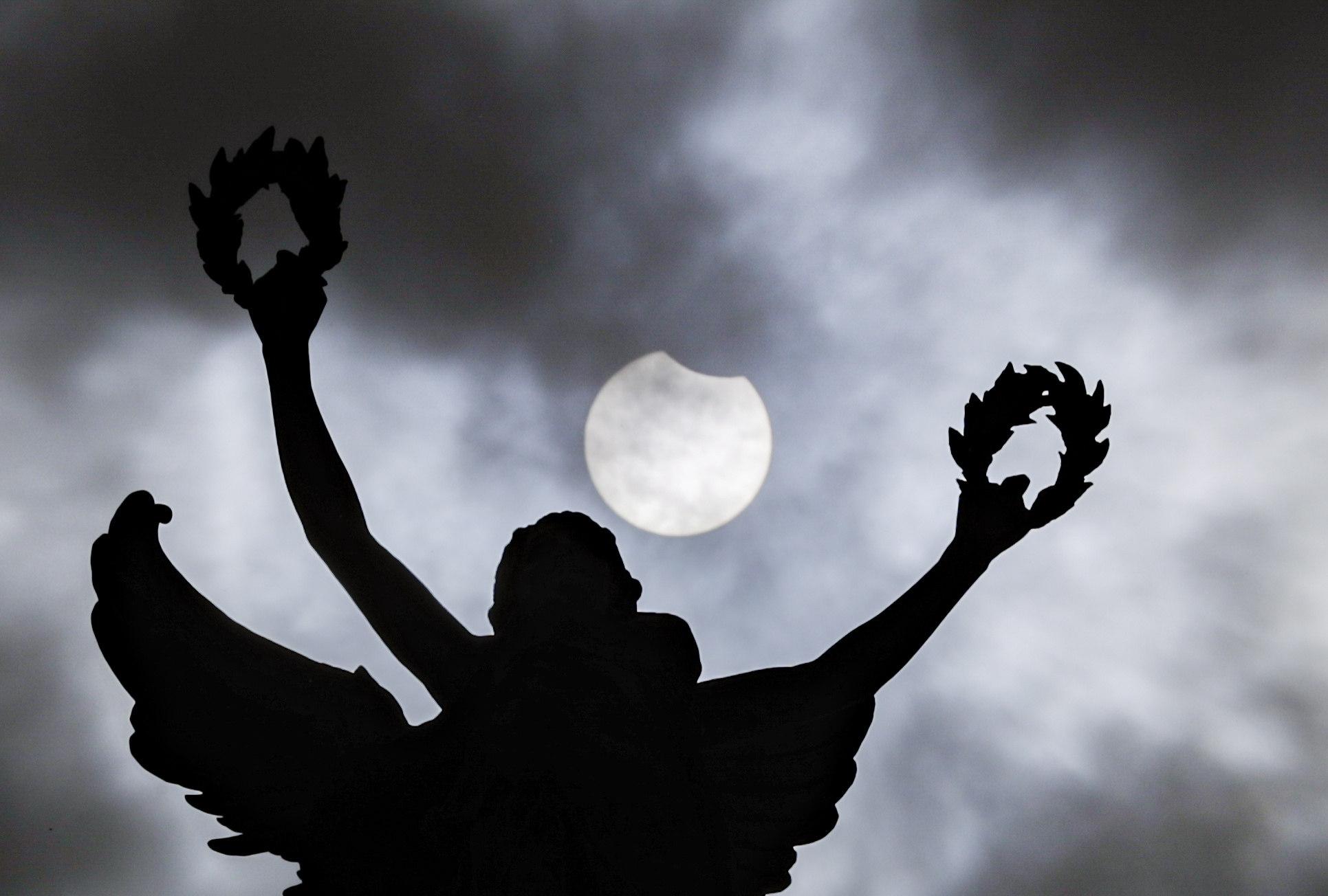 El fenómeno astronómico, visto detrás de una estatua en el parque Jubilee de Bruselas.