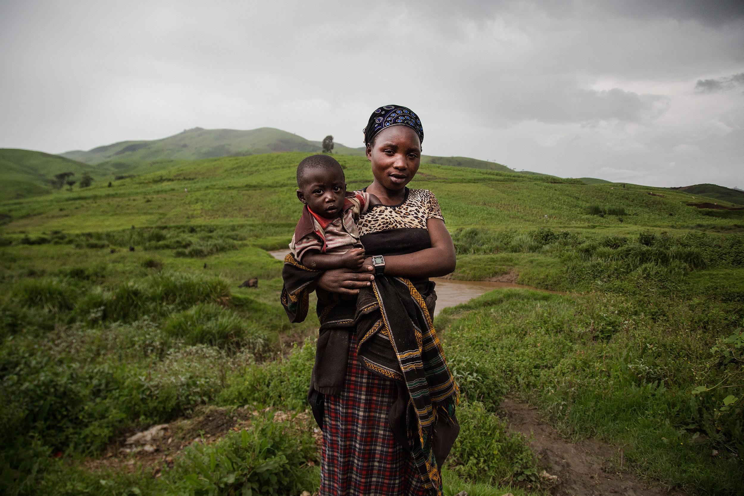 Asefili, una trabajadora del coltán, mira a cámara con su hijo en brazos en medio del campo.