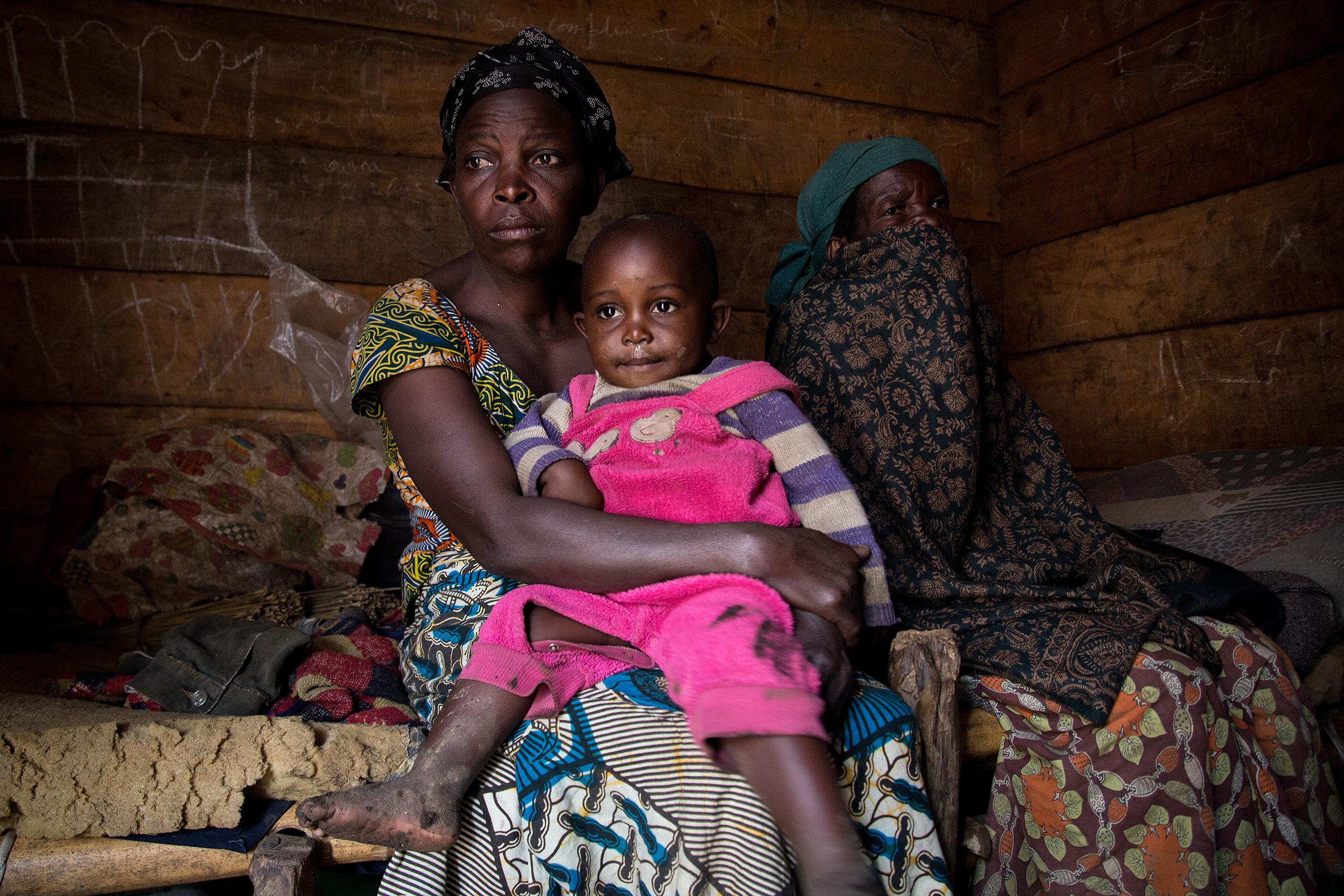 Loabauma con su hija pequeña en brazos, junto a una anciana con el rostro tapado, posan sentadas sobre el jergón de su vivienda.