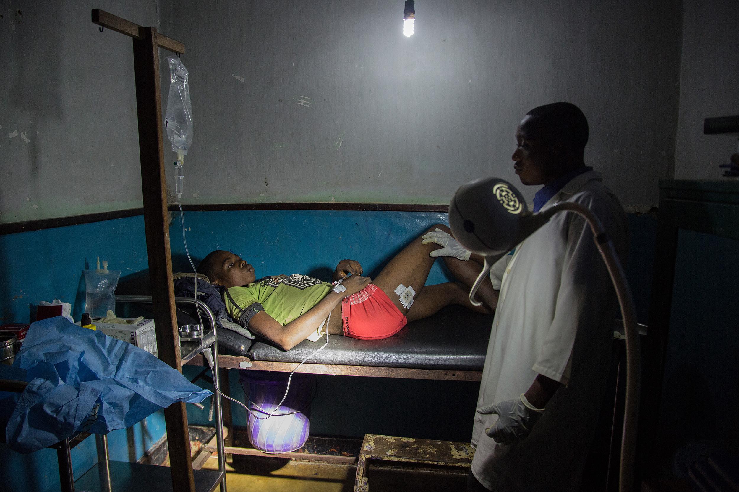 Un joven yace en una cama del hospital de Lulingu, bajo la supervisión de un médico. Luce un vendaje en una de sus piernas.