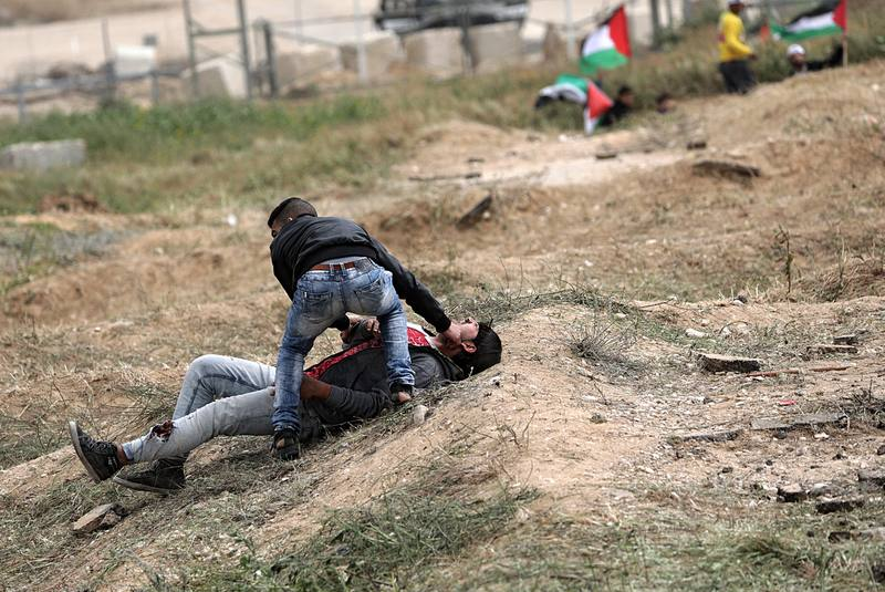 Un palestino ayuda a un compañero herido durante los enfrentamientos con soldados israelíes en el este de Beit Hanun, norte de la Franja de Gaza