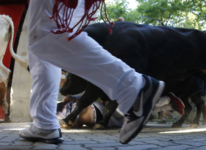 Un toro pisotea a un corredor