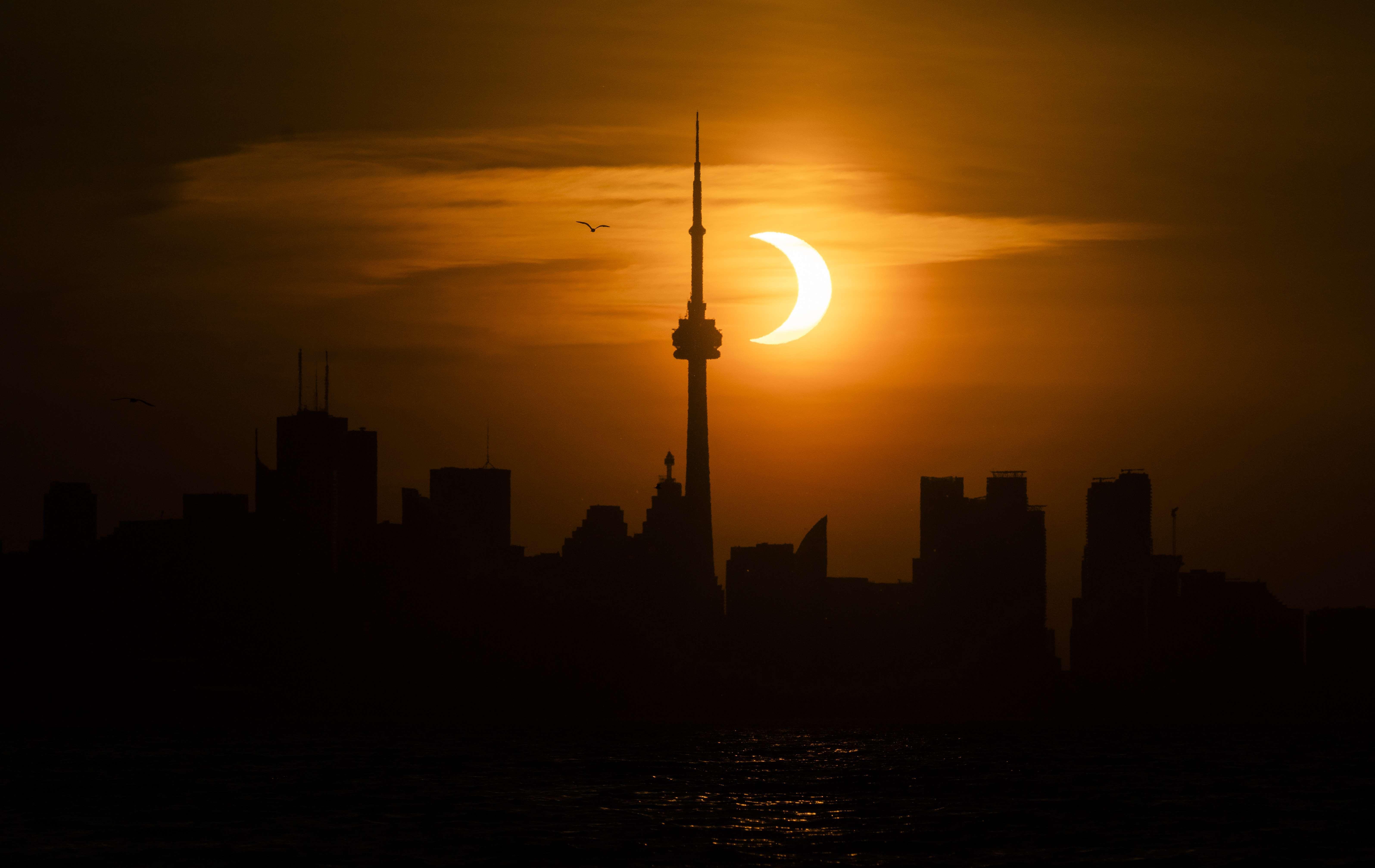 El eclipse de Sol, recortado sobre el 'skyline' de Toronto, en el que destaca la Canadian National Tower.