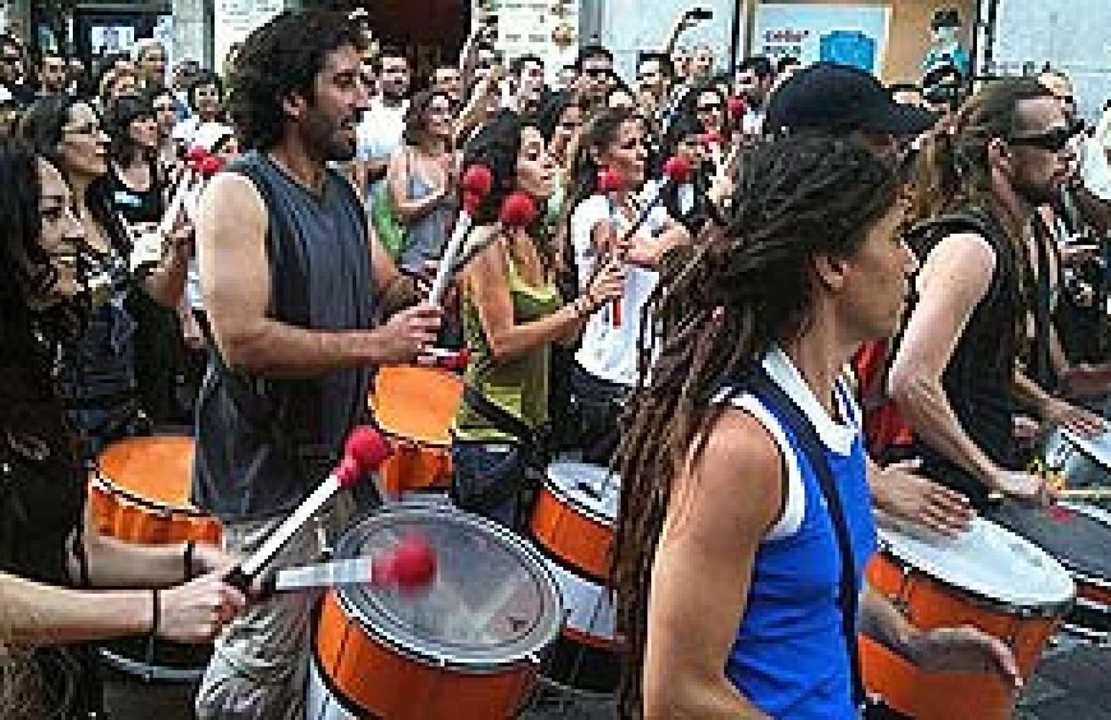 Decenas de personas hacen sonar sus tambores en una 'batucada' espontánea en la Puerta del Sol de Madrid.