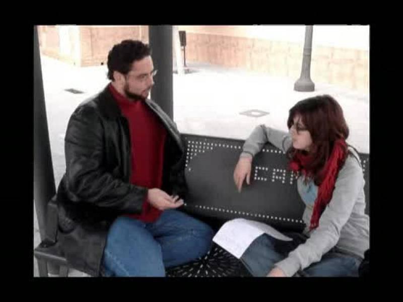 Dos estudiantes charlando sobre el plan Bolonia en un banco de la universidad.