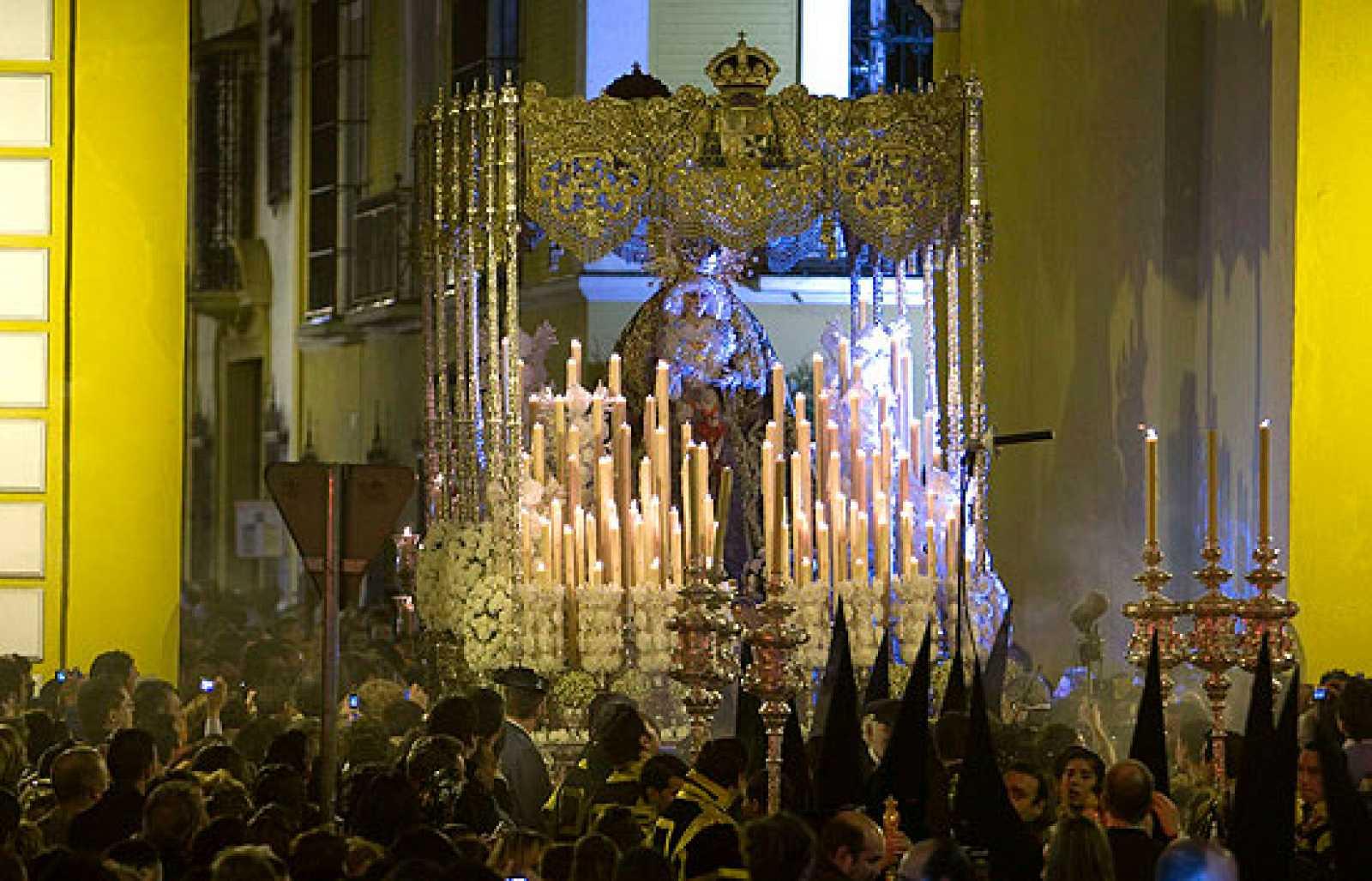 Cientos de miles de personas celebran la Madrugá del Viernes Santo en Sevilla.
